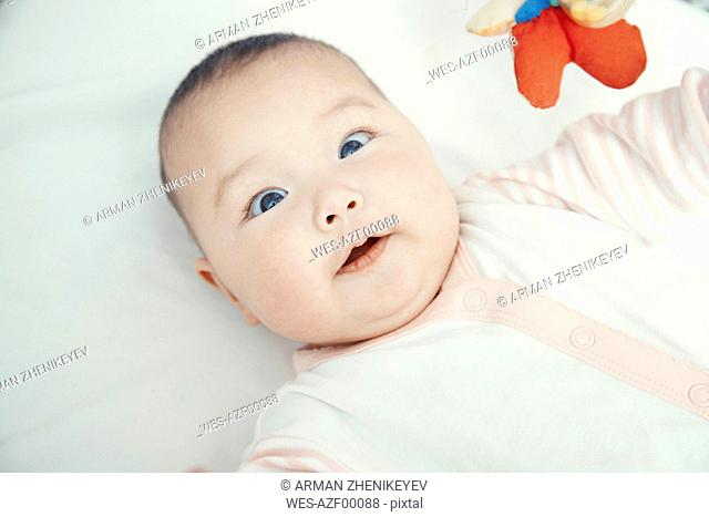 Smiling baby lying on bed, portrait