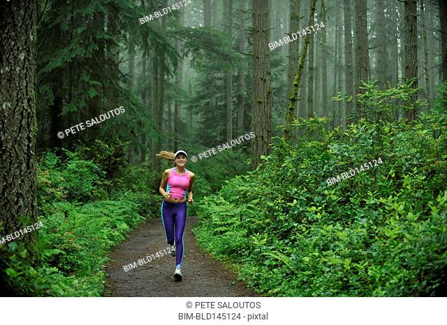 Caucasian woman running on remote path