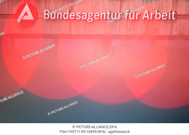 11 July 2019, Bavaria, Nuremberg: Luminaires of a parking lot pillar light up in front of the lettering of the headquarters of the Federal Employment Agency...
