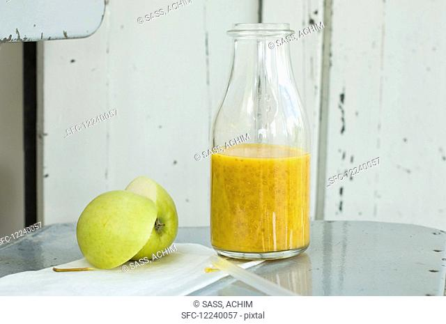A mango and orange smoothie with chia seeds in a bottle on an old chair with an apple