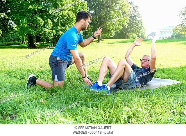 Man doing strength training on a meadow while his personal trainer watching him