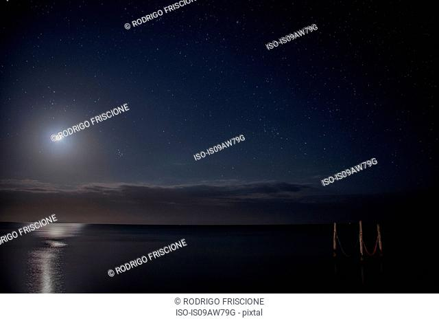 Starry sky and full moon illuminate iconic hammocks over waters, Isla Holbox, Mexico