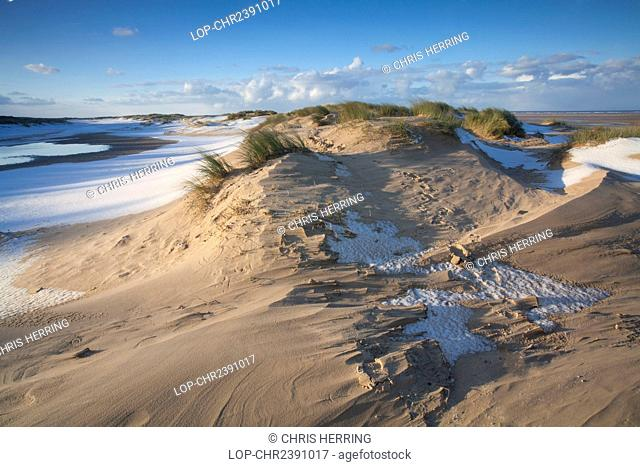 England, Norfolk, Holkham Bay. Winter snow on the beach and sand dunes at Holkham Bay on the North Norfolk Coast