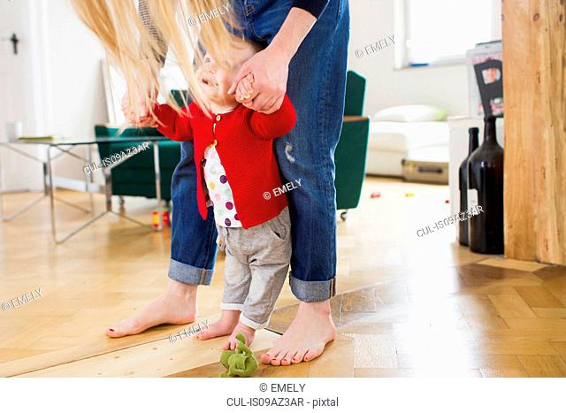 Baby girl holding mothers hands to take first steps