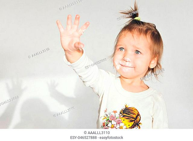 the little girl got her hand dirty in the cake. Isolated shot on white background. dirty hand of a child in the food