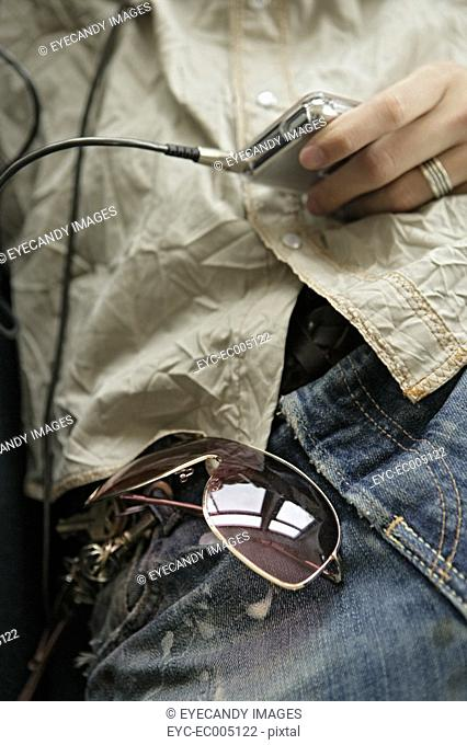 Young man holding music player and sunglasses in pocket, midsection