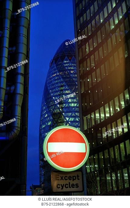 Sign of prohibited direction in front of The Gherkin building and an office building of modern architecture with lighted windows at dusk in the city of London