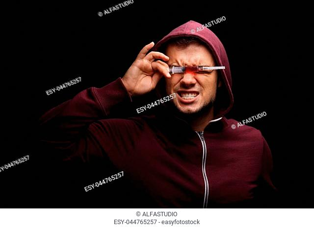 Expressive guy in a dark red hoodie with a drug syringe on a black background. An obsessed with drugs freak suffering from deadly addiction