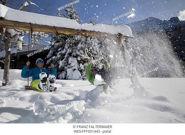 Germany, Bavaria, Inzell, couple having fun on swings in snow-covered landscape