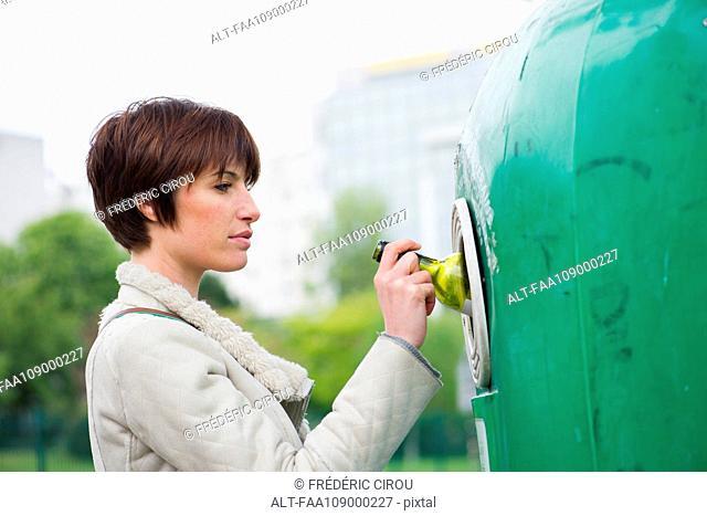 Woman putting wine bottle into recycling bin