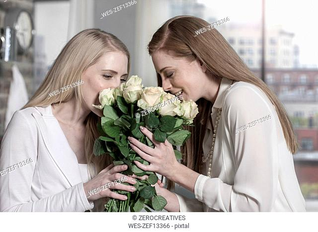 Two young women smelling roses at home