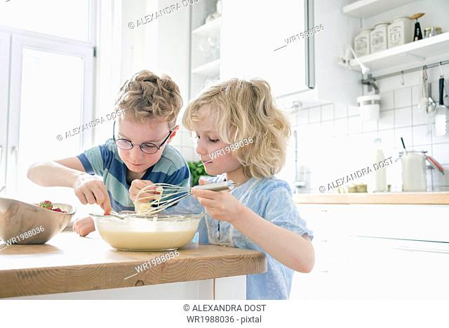 Brother and sister in kitchen cooking together