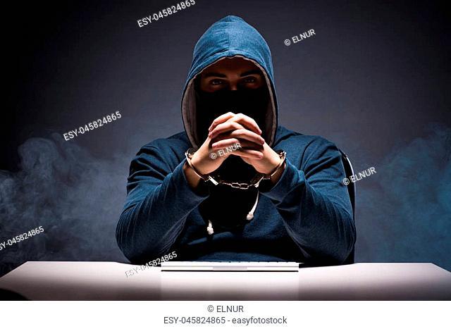 Computer hacker working in dark room