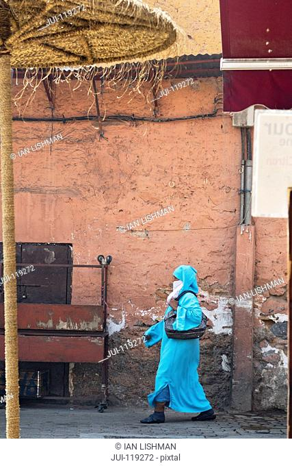 Local woman in traditional dress walking through Souk area, Marrakech, Morroco