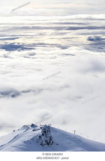 A Chairlift Can Be Seen Running Along A Ridge In Front Of A Large Bank Of Clouds At Cerro Catedral In Argentina