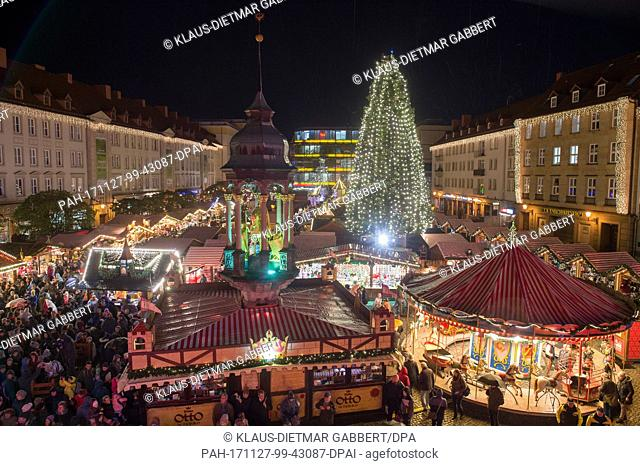 A Christmas tree glows with light while visitors walk over the grounds of the Christmas market in Magdeburg, Germany, 27 November 2017
