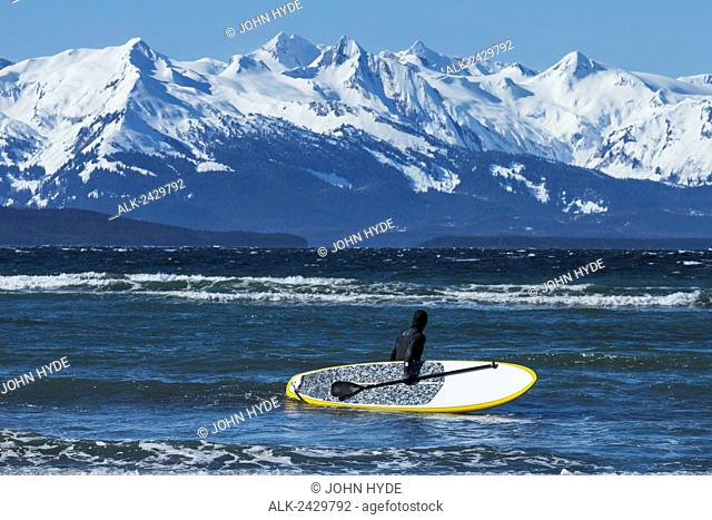 Person takes a paddle board into Lynn Canal on a windy winter afternoon near Eagle Beach State Recreation Area, Juneau, Southeast Alaska