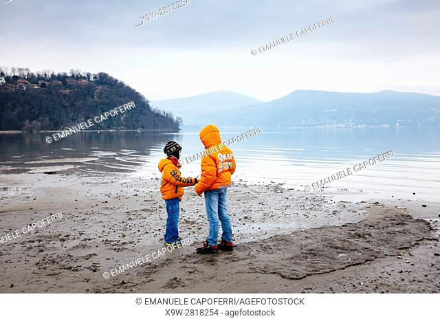 Children in winter on Lake Maggiore beach