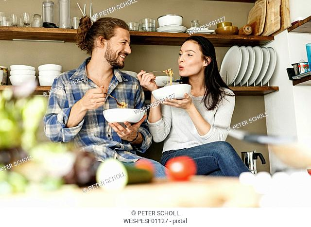 Happy couple sitting in kitchen, eating spaghetti