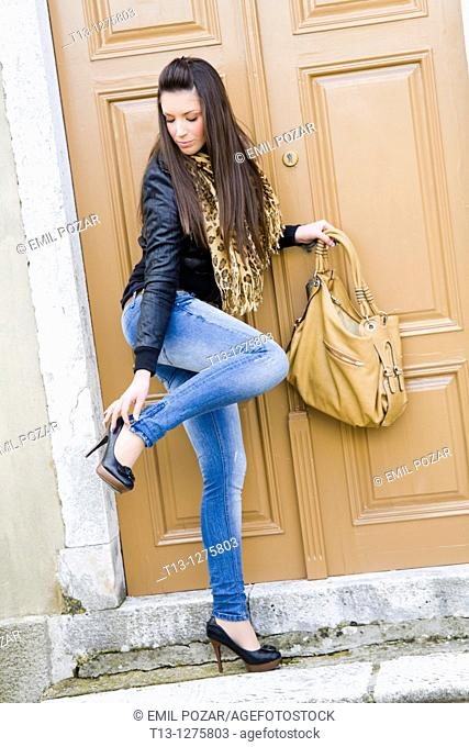 Unzipping denim pants young woman