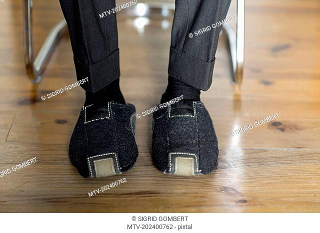 Low section view of a businessman wearing slippers, Freiburg im Breisgau, Baden-Württemberg, Germany