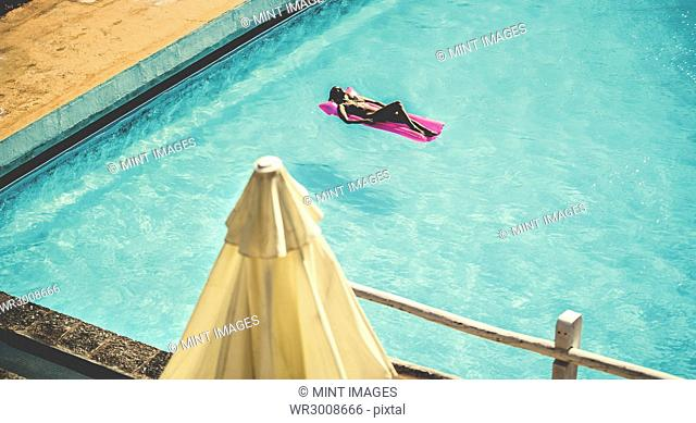 High angle view of a young woman lying on a pool raft in a swimming pool