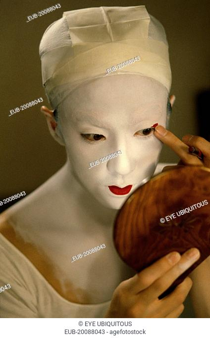 Kabuki actor Tamasaburo looking in hand mirror to apply make-up for role of Izayoi the courtesan turned crook in 'The Village School'