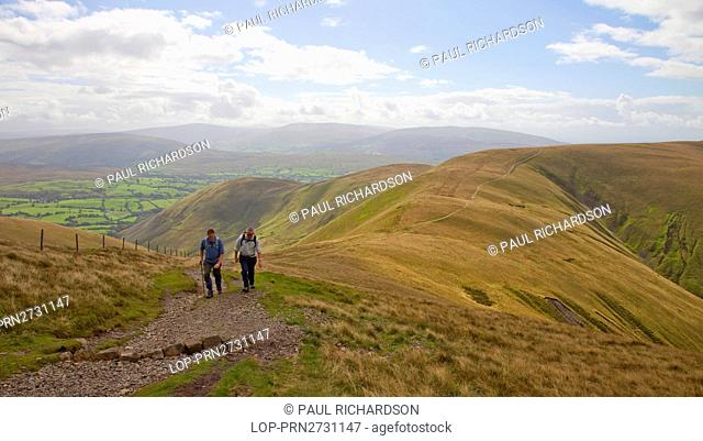England, Cumbria, Sedbergh. Two hillwalkers walking the track up to Calders from Arant Haw in the Howgill Fells