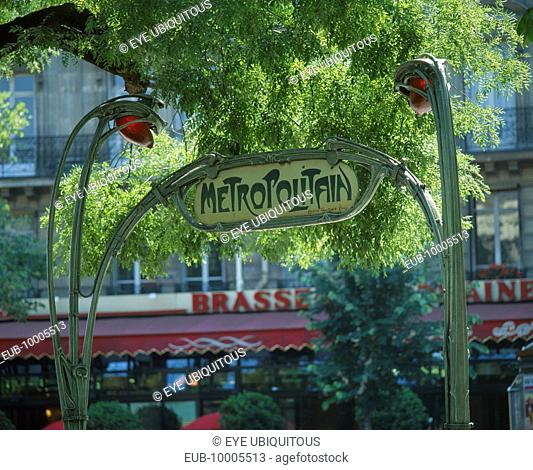 Art Nouveau `Metropolitain' sign in green wrought iron under tree branches
