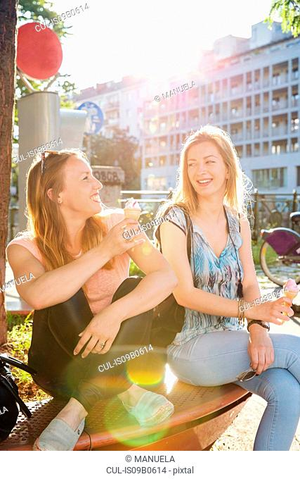 Two adult female friends eating ice cream cones on city bench, Vienna, Austria