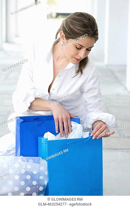 Young woman searching in the shopping bag