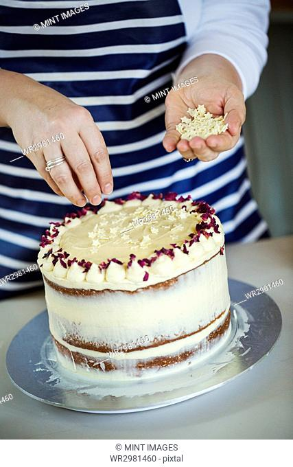 Close up of person wearing a blue and white stripy apron sprinkling white chocolate stars on a cake