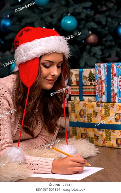 Beautiful attractive brown haired girl pending Christmas dressed in cap of Santa Claus laying on stomach writing congratulation letter on white clear paper...