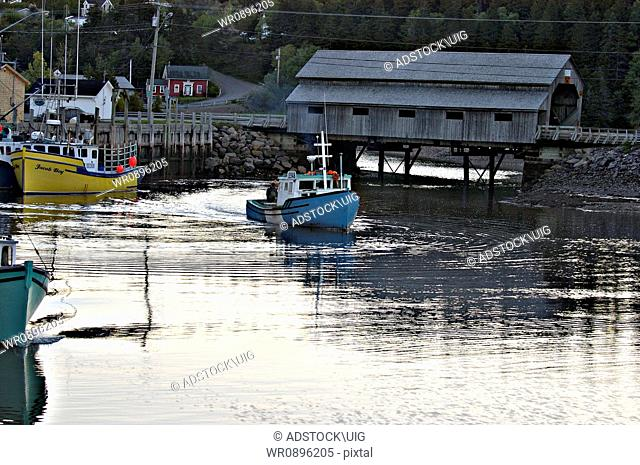 A lobster fishing boat steams out of the harbour towards the fishing grounds