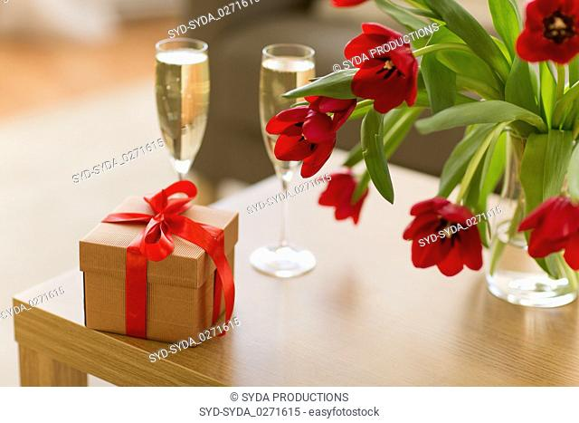gift box, champagne glasses and flowers on table