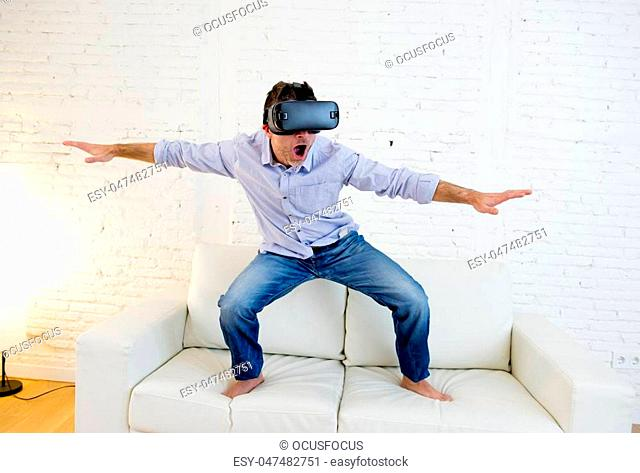 young modern man at home standing on living room sofa couch excited using 3d goggles watching 360 virtual reality vision enjoying the fun cyber experience in...