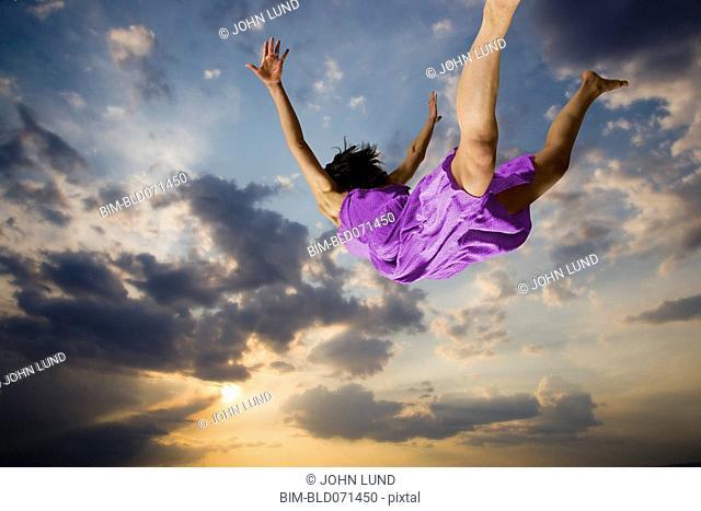 Hispanic woman flying through sky