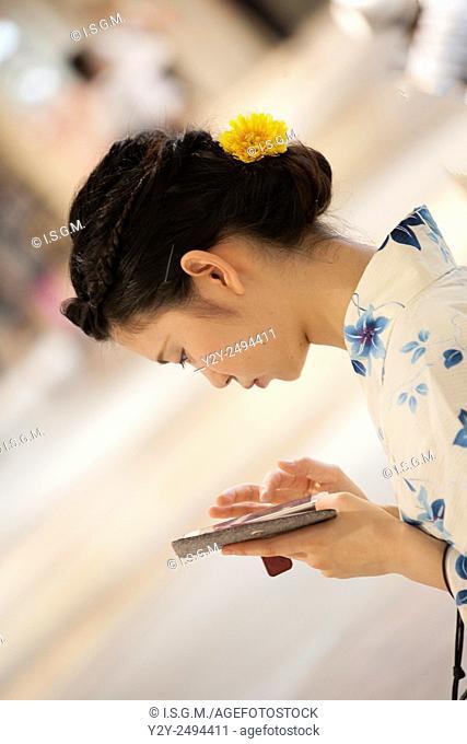 Japanese girl with smartphone at Hakata train Station, Japan