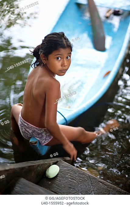 Guatemala, Mayan girl with dug out canoe