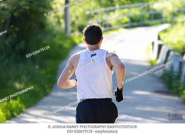 EUGENE, OR - MAY 7, 2017: Runner heads down the river path at mile 10 of the 2017 Eugene Marathon race held on the University of Oregon campus