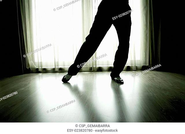 Legs of man dancing with white shoes and black