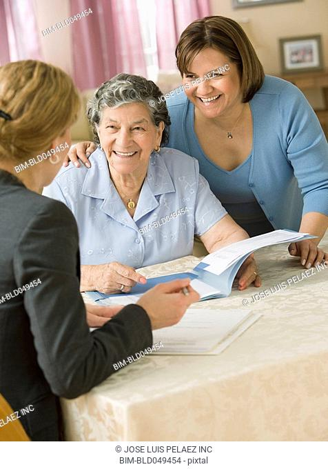 Senior Hispanic woman discussing paperwork with businesswoman