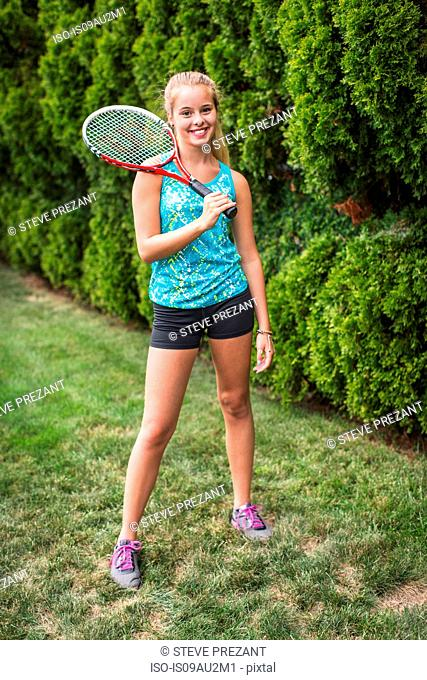 Teenager with tennis racket in garden