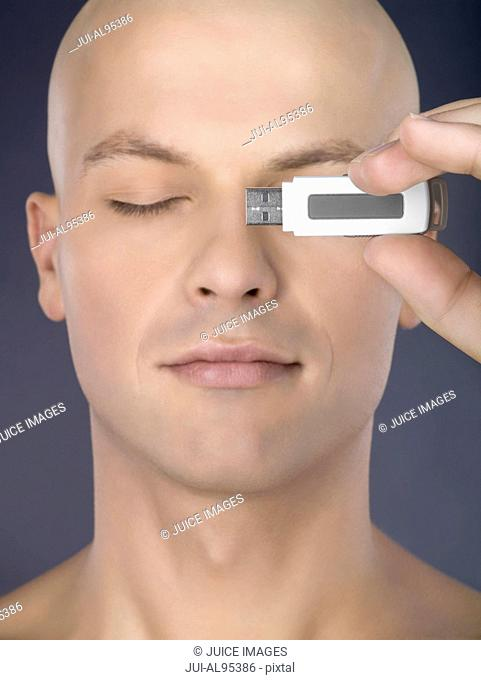 Man holding usb drive in front of eye