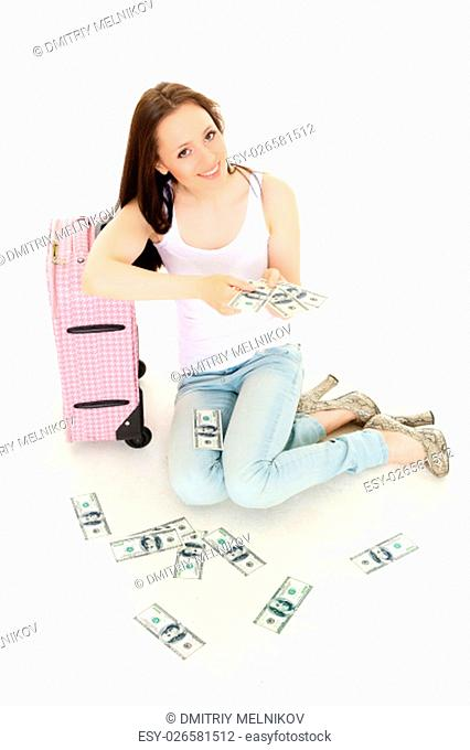 Young happy woman with suitcase and money sits on a white background. Vacation