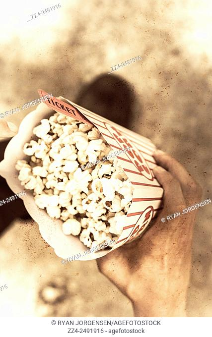 Top down view on a vintage audience member holding a box of buttered popcorn with ticket. Movie nostalgia