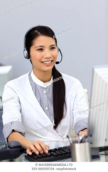 Smiling businesswoman with headset on working at a computer