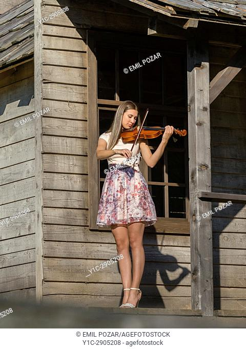 Young woman violin player in wild west environment. Croatia