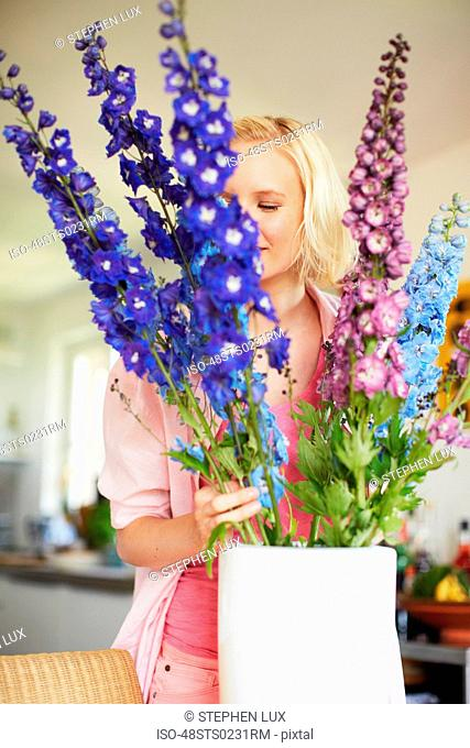 Woman arranging flowers in kitchen