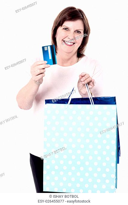 Happy senior woman paying for shopping by credit card